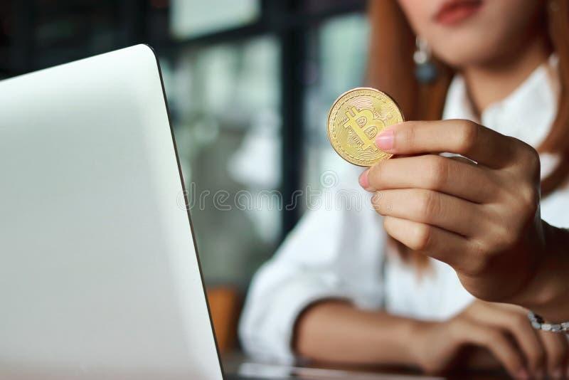 Dé el ` s de la mujer de negocios que sostiene la moneda de oro del bitcoin del cryptocurrency Dinero virtual en digital imagenes de archivo