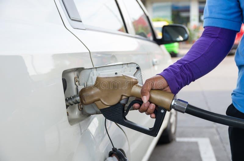 Dé el surtidor de gasolina del control para añadir el combustible en coche en la estación de servicio imágenes de archivo libres de regalías