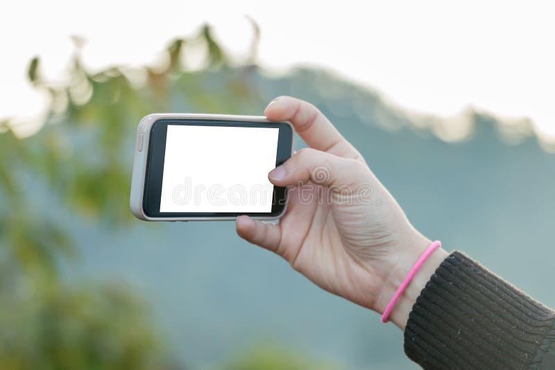 Dé el teléfono celular de tenencia para tomar una foto, pantalla en blanco en blanco imagen de archivo libre de regalías