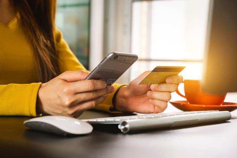 Dé el teléfono móvil olding con actividades bancarias en línea de la tarjeta de crédito foto de archivo