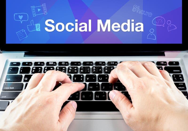 Dé el tipo en el ordenador portátil con medios sociales en la pantalla con la falta de definición b azul foto de archivo libre de regalías