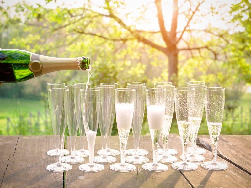 Dé el vino de colada en los vidrios de flauta de champán foto de archivo