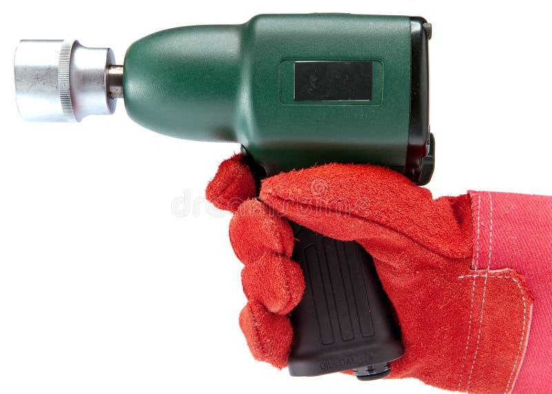 Dé en un guante de trabajo sostiene la llave de impacto del aire en un fondo blanco fotografía de archivo libre de regalías