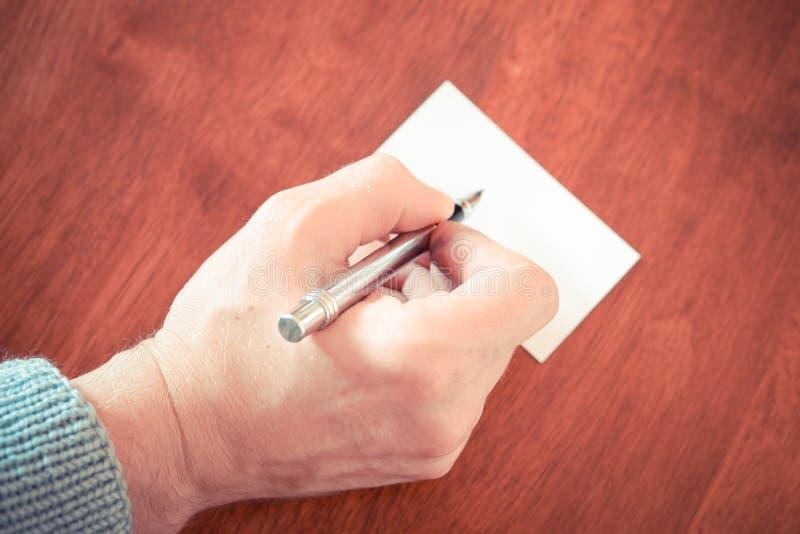 Dé a escritura con una pluma en trozo de papel la tabla de madera marrón fotografía de archivo libre de regalías
