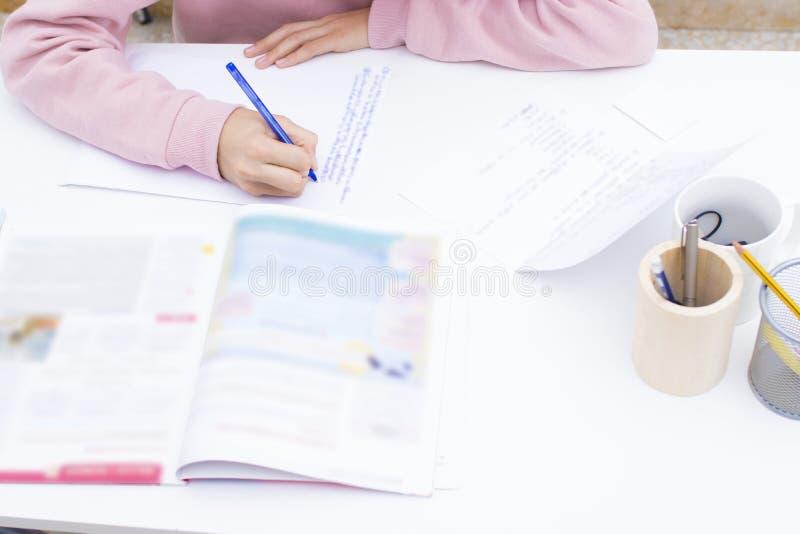 Dé estudiar y la escritura en el escritorio de la escuela fotos de archivo