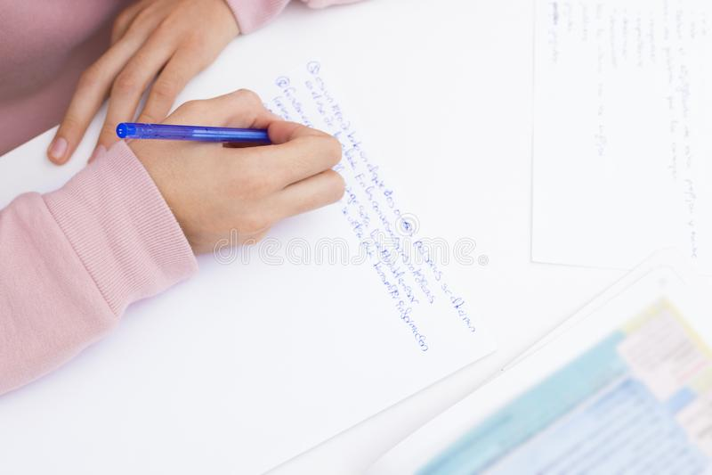 Dé estudiar y la escritura en el escritorio de la escuela imagen de archivo libre de regalías