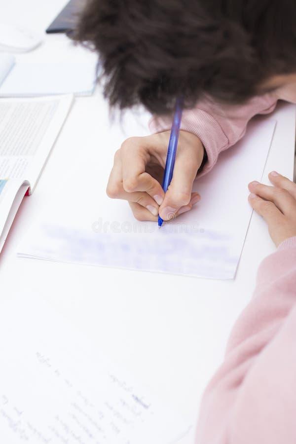 Dé estudiar y la escritura en el escritorio de la escuela foto de archivo