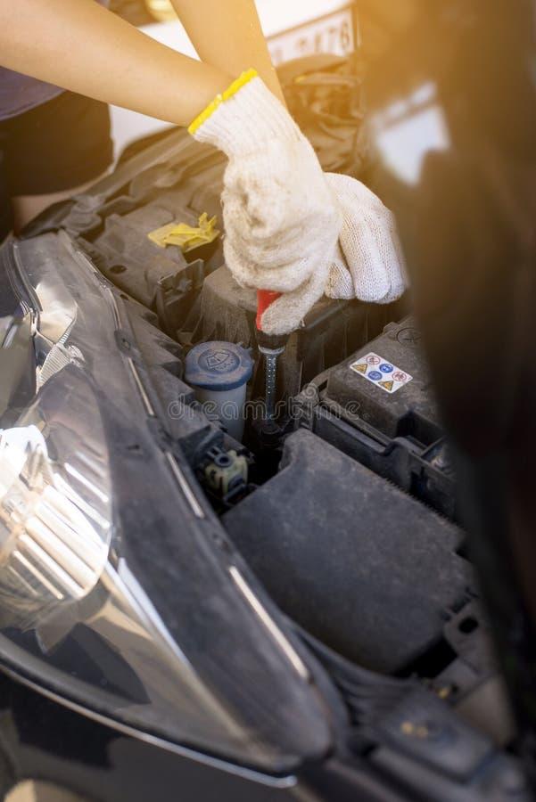 Dé la batería de coche de la fijación del ingeniero del mecánico en el garaje, mantenimiento del coche del concepto imagen de archivo libre de regalías