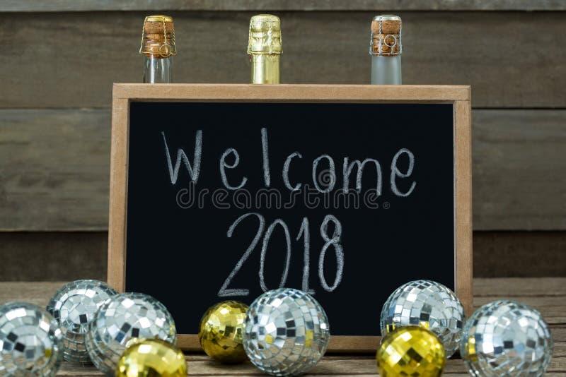 Dé la bienvenida a 2018 escrito en tablero de la pizarra con las chucherías y la botella del champán foto de archivo libre de regalías