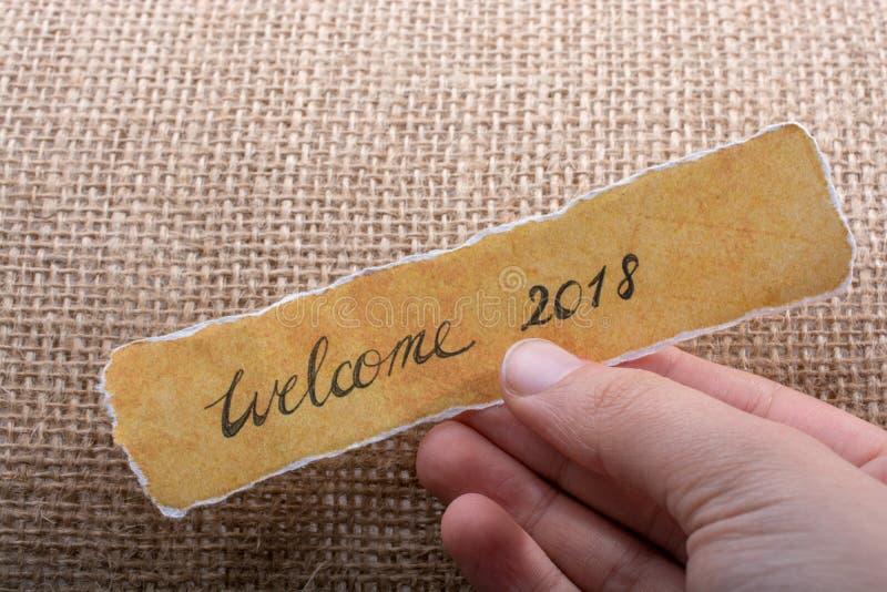 Dé la bienvenida a 2018 redacciones escritas en un papel rasgado amarillo foto de archivo libre de regalías