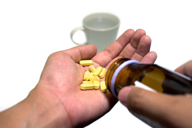 Dé la colada fuera de píldoras de una medicina de la botella en otra mano fotos de archivo libres de regalías