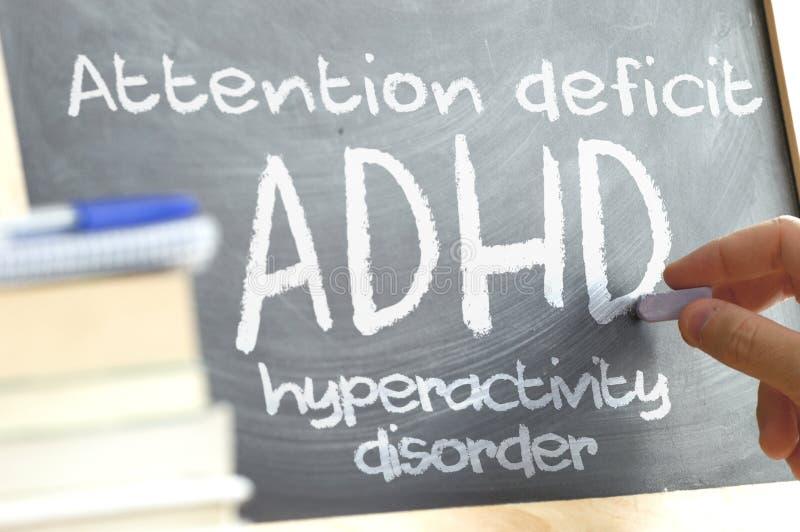 Dé la escritura en una pizarra en una clase con la palabra ADHD escrita encendido Algunos libros y materiales de la escuela imagenes de archivo