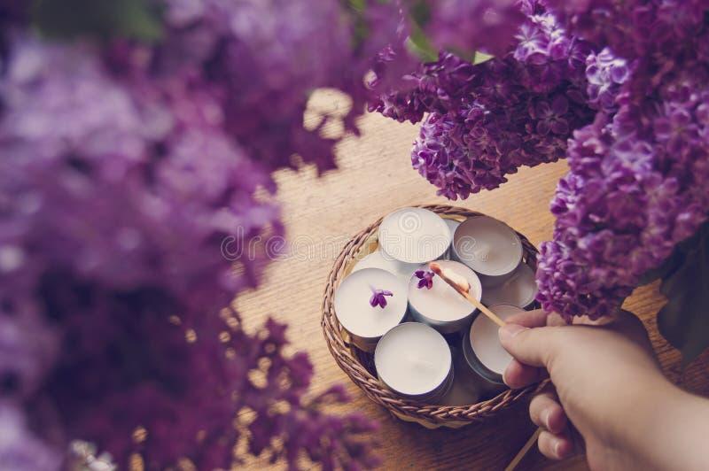 Dé la iluminación de pequeñas velas blancas en una cesta y una lila fotos de archivo libres de regalías
