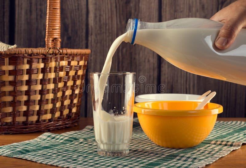 Dé la leche de colada en el vidrio imagenes de archivo