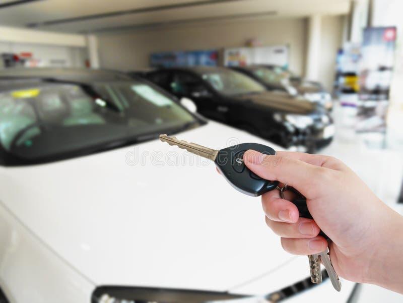 Dé la llave del coche del control con la sala de exposición del coche de la falta de definición imagen de archivo libre de regalías