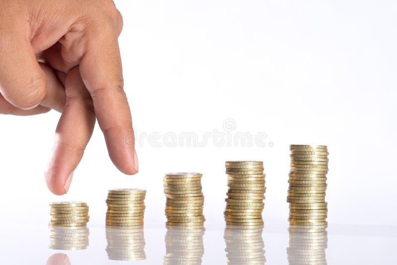 Dé la mano humana que pone la moneda al dinero, ideas del negocio imagen de archivo libre de regalías