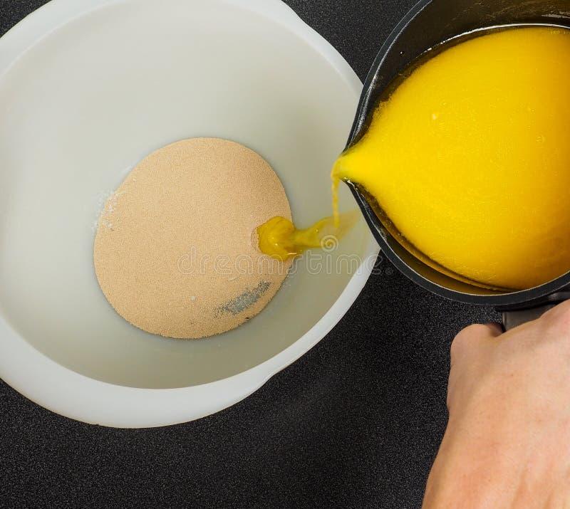 Dé la mantequilla derretida de colada en un cuenco blanco con levadura seca imagen de archivo libre de regalías
