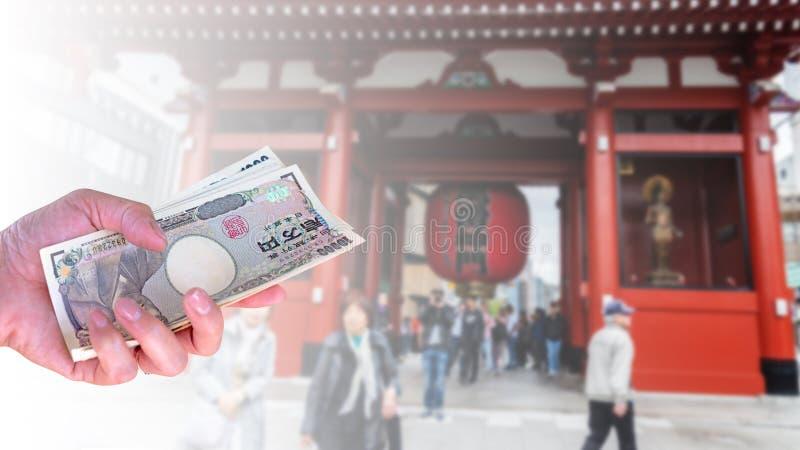 Dé la mujer con los billetes de banco japoneses de los yenes de la moneda en empañado detrás fotos de archivo libres de regalías