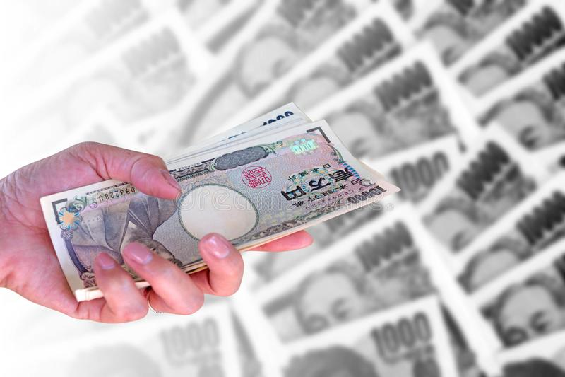 dé la mujer que sostiene billetes de banco japoneses de los yenes de la moneda encendido fotos de archivo libres de regalías