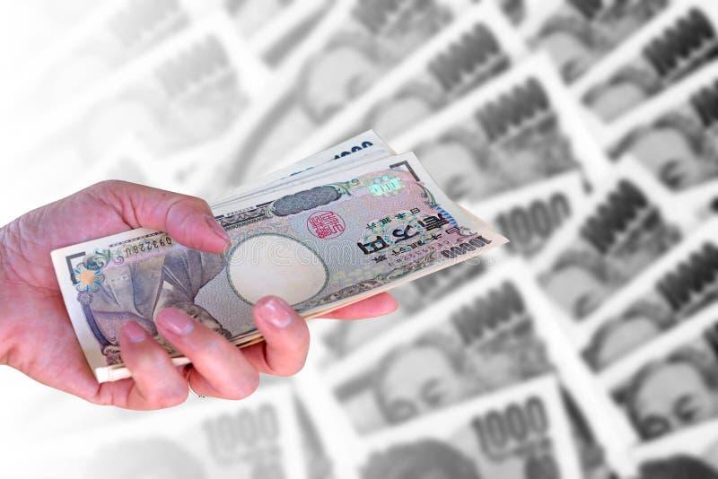 dé la mujer que sostiene billetes de banco japoneses de los yenes de la moneda encendido foto de archivo libre de regalías