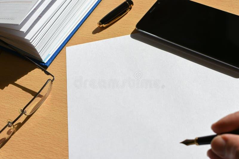 Dé la pluma en una hoja de papel en una mesa de madera en la oficina, smartphone, efectos de escritorio, vidrios, espacio de la e fotografía de archivo