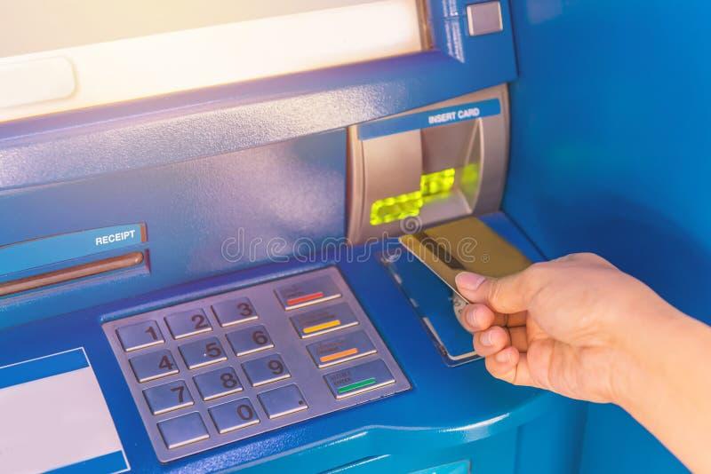 Dé la tarjeta de crédito del parte movible al cajero automático del banco de la atmósfera para retiran el MES foto de archivo libre de regalías