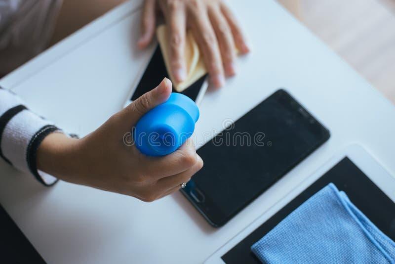 Dé a limpieza femenina el teléfono elegante sucio en la pantalla con el paño de la microfibra imagen de archivo libre de regalías