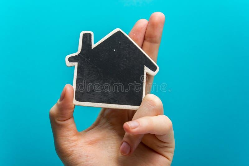 Dé llevar a cabo la figura de la casa del Libro Blanco en fondo azul Concepto 6 de las propiedades inmobiliarias Copie la opinión foto de archivo libre de regalías