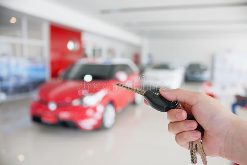 Dé llevar a cabo llaves del coche en la nueva sala de exposición del coche imagen de archivo