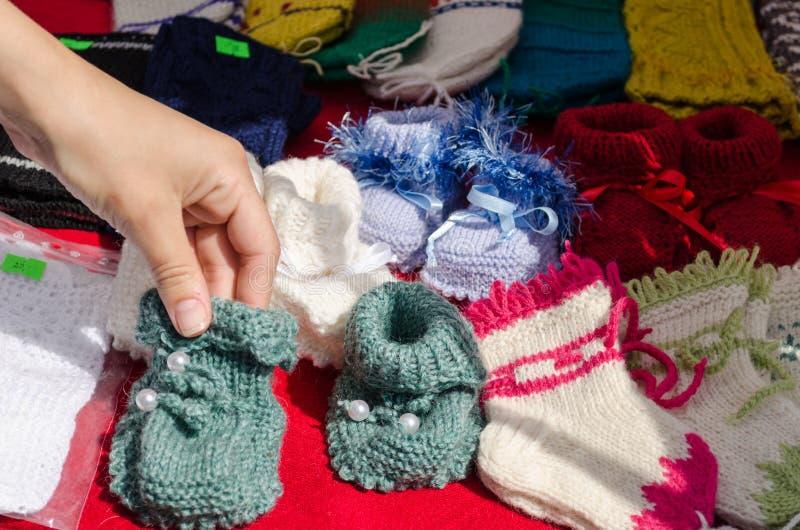 Dé los zapatos de bebé acogedores calientes hechos punto las lanas de la toma imagen de archivo libre de regalías