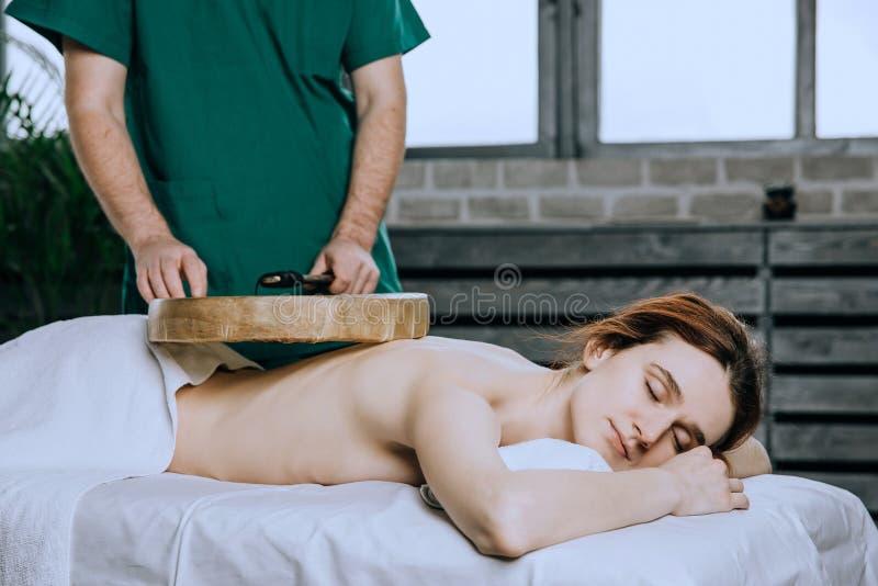 Dé masajes a la parte posterior de una mujer con una pandereta Métodos no tradicionales de medicina Cara relajada hermosa de un imagen de archivo libre de regalías