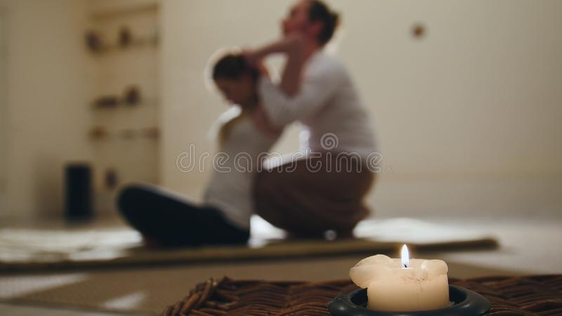 Dé masajes a la sesión en velas - terapia tradicional de Tailandia para el modelo femenino joven, de-enfocada fotografía de archivo libre de regalías