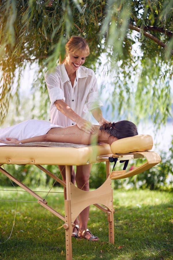 Dé masajes a la terapia, concepto de la atención sanitaria, mentira femenina en cama del masaje fotografía de archivo
