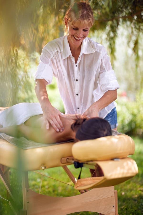 Dé masajes a la terapia, concepto de la atención sanitaria, mujer que miente en cama del masaje foto de archivo libre de regalías