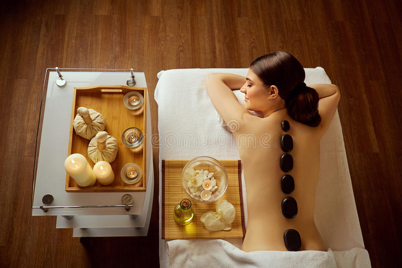 Dé masajes a las piedras encendido detrás de una mujer en el salón del balneario fotos de archivo libres de regalías