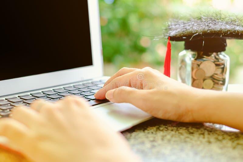 Dé mecanografiar en el ordenador portátil del ordenador con el casquillo académico cuadrado y fotos de archivo libres de regalías