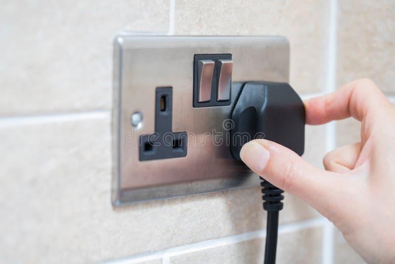 Dé poner el enchufe en el zócalo de la electricidad foto de archivo libre de regalías