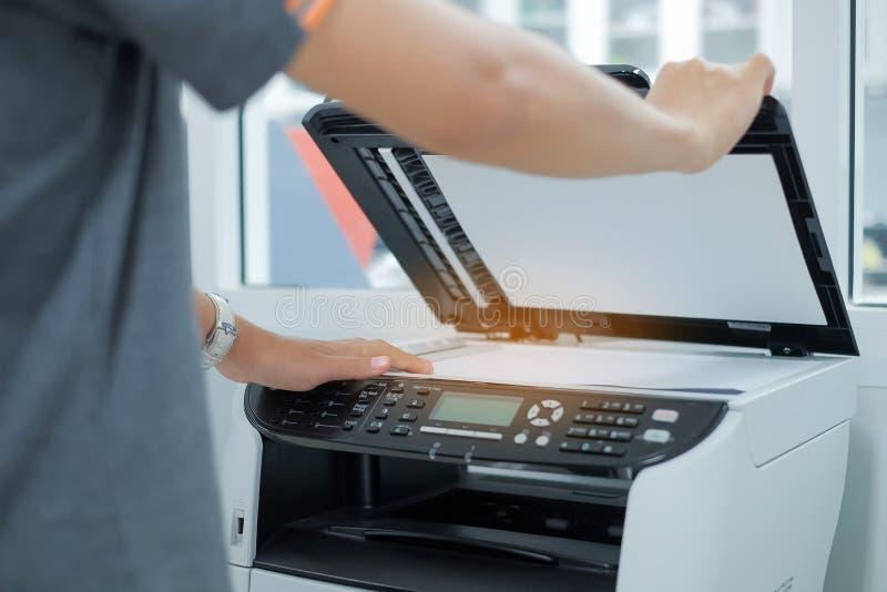 Dé poner un papel del documento en la máquina de la copia del escáner o del laser de impresora en oficina fotos de archivo