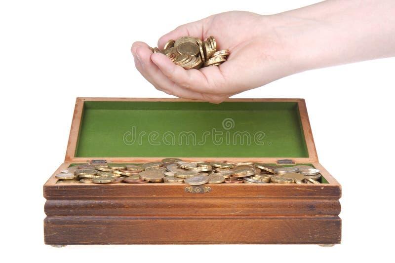 Dé por completo de monedas sobre un pecho de tesoro foto de archivo