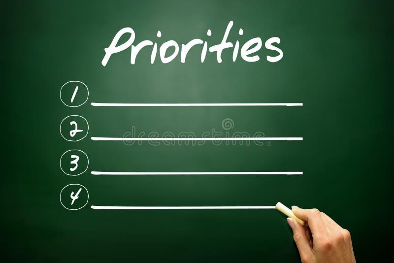 Dé a prioridades exhaustas el concepto en blanco de la lista en la pizarra imágenes de archivo libres de regalías