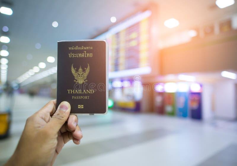 Dé que muestra el pasaporte de Tailandia en el aeropuerto fotografía de archivo