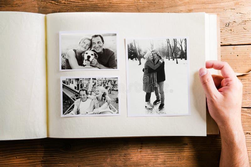 Dé sostener el álbum de foto con las imágenes de pares mayores estudio fotos de archivo