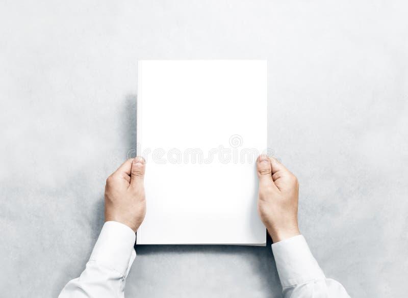 Dé sostener el diario blanco con la maqueta de la cubierta en blanco imagenes de archivo