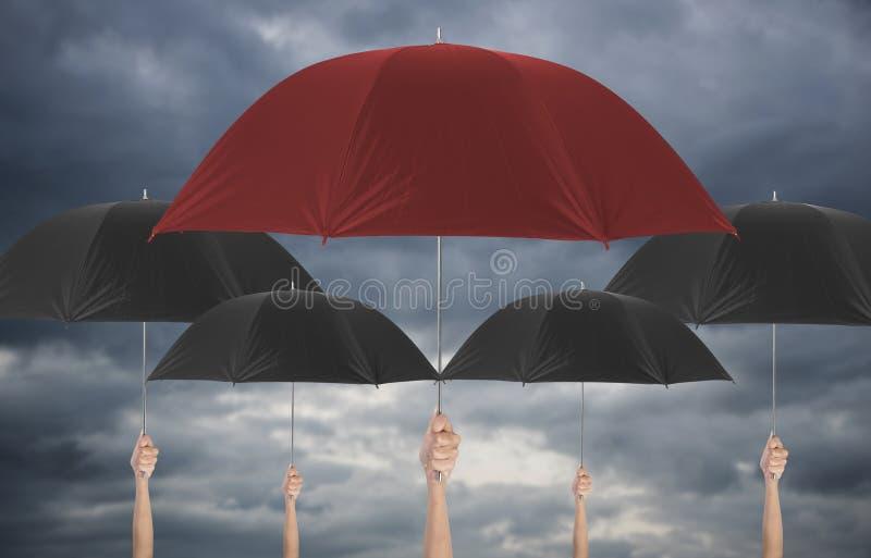 Dé sostener el paraguas rojo diferente entre umbella negro foto de archivo