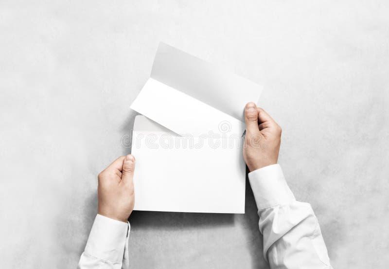 Dé sostener el sobre en blanco blanco y la maqueta doblada del prospecto, aislados fotos de archivo libres de regalías