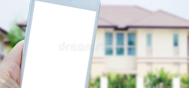 Dé sostener el teléfono elegante con el espacio en blanco en la pantalla sobre casa borrosa fotografía de archivo