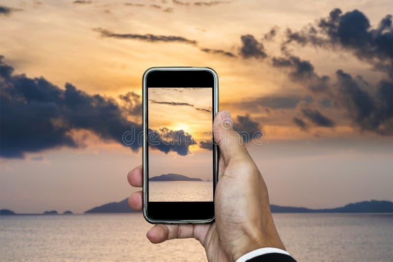 Dé sostener el teléfono elegante que toma la foto del paisaje de la puesta del sol en la composición vertical, en tiempo de vacac imagenes de archivo