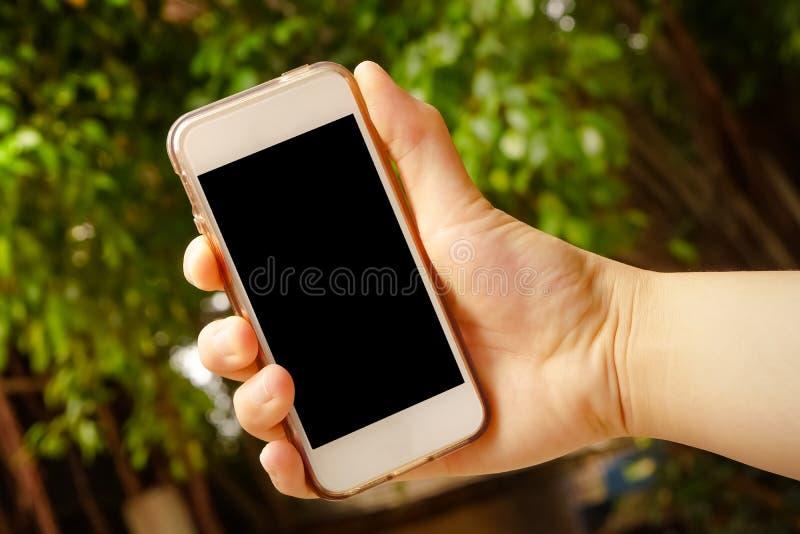 Dé sostener el teléfono elegante (teléfono móvil) con la naturaleza en backgroun imagen de archivo
