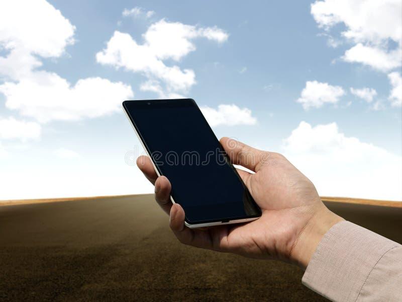 Dé sostener el teléfono móvil con la pantalla en blanco en backgroun vacío del camino foto de archivo libre de regalías
