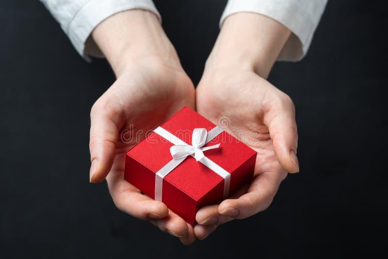 Dé sostener la caja para un regalo aislado en negro imagenes de archivo